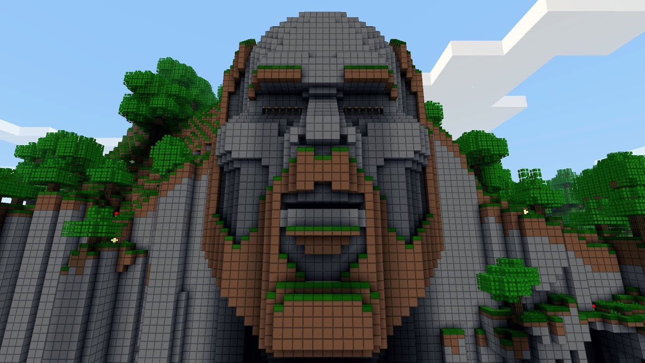 A statue of Minecraft creator Notch's head made of stone and dirt on a cliffside